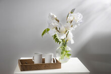 A Bouquet Of Three White Irises And A Fern In A Transparent Vase On The Table. Two Ceramic Tea In The Tray. Breakfast