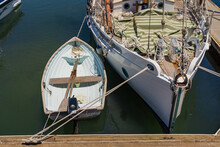 A Small Row Boat Tied Next To The Bow Of A Large Yacht
