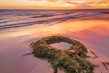 A Dramatic Sunset Reflecting On A Wet Sandy Beach Around A Solitary Circular Rock Pool