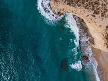 Aerial View Of Waves Crashing On Rocky Coastline