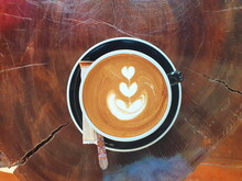 Top View Of Hot Coffee: Frothed Milk Latte Art - In A Heart-shaped Cup And A Beautiful Plant. Served In A Ceramic Mug And Black Coaster. With Stainless Steel Spoons And Sugar Sachets On A Wooden Table
