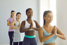 Group Meditation. Relaxed Afro American Young Woman Standing With Folded Arms In Namaste Gesture At Group Yoga Class. Woman Meditates Among Other Caucasian Women In A Bright Hall. Selective Focus.