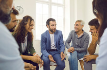 Young But Experienced Business Coach Sharing Advice With A Group Of People. Team Of Positive Employees Of Different Ages Meeting For A Talk And Interesting Discussion With A Corporate Psychologist