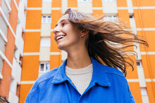 Happy Woman Standing In City And Laughing