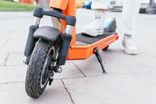 Crop Person Standing Near Electric Scooter In City