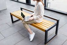 Young Woman Holding Laptop And Smartphone Sitting On A Bench
