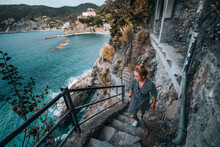 Young Female Climbing Stairs On Coastal Path In Cinque Terre
