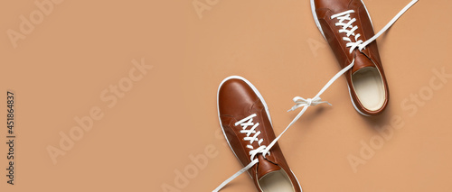 Leather brown men's sneakers with white laces and rubber soles on beige background. Flat lay top view. Men's sports casual shoes. Fashionable sneakers. Male fashion hipster footwear Minimal background