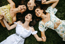 Four Young Women Lying On Grass, Having Good Time, Laughing, Top View.