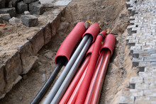 A Large Number Of Electric And High-speed Internet Network Cables In Red Corrugated Pipe Are Buried Underground On The Street Covered With Cobblestones.