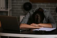 Young Depressed Businesswoman In Dark Office