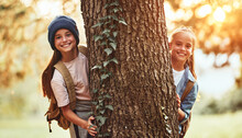 Happy School Girls Hugging Tree In Forest And Smiling At Camera During Camping Activity In Nature