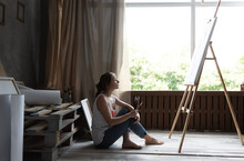 In An Atmospheric Art Studio, A Beautiful Caucasian Woman Artist Sits On The Floor Looking At The Easel And Examines The Picture She Has Painted.