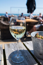 Glass Of White Wine Served On Outdoor Terrase With Seaview, Summer Vacation