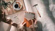 Topview Girl Playing Kalimba, Acoustic Music Instrument From Africa. Kalimba Concept.