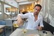 Przystojny, uśmiechnięty, dojrzały brunet z lampką wina podczas klimatycznej kolacji we włoskich klimatach.