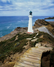 Set Of Wooden Steps Leading Down To Castle Point Lighthouse On Rocky Cliff Edge And Blue Pacific Ocean Below