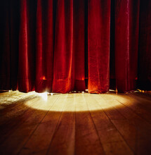 Spotlight Shining On Red Stage Curtains And Wooden Floor