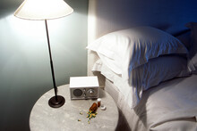 Lamp Switched On Resting On Bedside Table Next To Bed