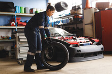 Mixed Race Female Car Mechanic Wearing Overalls, Holding Tire