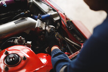 Close Up Of Hands Of Mixed Race Female Car Mechanic Wearing Overalls, Checking Oil Level