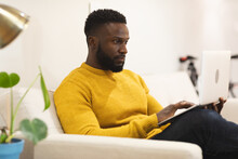 Thoughtful African American Male Business Creative Sitting On Sofa In Workplace Lounge And Working