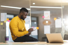 Serious African American Male Business Creative Sitting On Desk And Making Notes