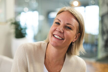 Smiling Caucasian Female Business Creative Looking At Camera At Workplace Cafeteria
