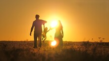 A Small Child Walks With Mom And Dad At A Bright Sunset In The Sky. Meet The Sunrise With Your Family While Traveling. Go Hiking With Your Mother And Father. Kid And Loving Parents Walk In The Park