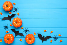 Halloween Paper Bats With Candies, Spiders And Orange Pumpkins On Blue Wooden Background