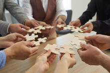 Team Of Business People Joining Pieces Of Jigsaw Puzzle, Closeup Shot Of Hands Holding Jigsaw Parts In Circle. Group Of Entrepreneurs Forming Coalition Or Alliance. Cooperation And Teamwork Concept