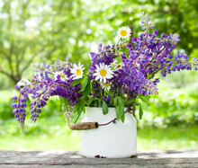 A Bouquet Of Purple Lupins And White Daisies In A Metal Can On A Wooden Table.