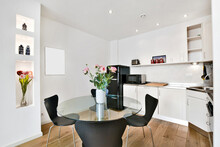 Modern Kitchen Interior With White Furniture, Glass Round Table, And Black Details