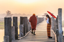 Burmese Girls Pay Homage To The Monks Passing By On The Bridge. Woman Wearing Traditional Clothes With Red Umbrella At U Bein Teak Bridge In Mandalay, Myanmar.