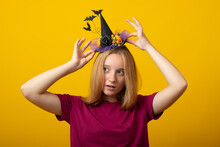 Halloween Party Girl. Happy Halloween Witch With A Black Hat. Beautiful Young Woman In Witches Hat And Costume On Yellow Background.