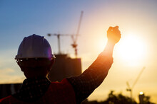 Silhouette Standing Shadow Engineer Working To Prepare Industrial Project Plans With Behind The Scenes Building Construction And Sunset.