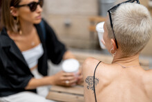 Stylish Female Couple Having Fun, Drinking Coffee At Cafe Outdoors. Homosexual Relation And Leisure Time In The City
