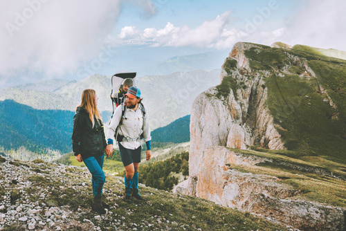 Family hike in mountains parents travel with child adventure vacations outdoor father and mother couple holding hands together healthy lifestyle