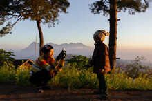 Young And Cute Mom Holding And Using Smartphone Takin Photo Of Her Little Son In The Morning Light During Camping And Travel On High Mountain And Forest
