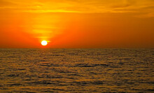 Sunset At Sea, Calm Ocean And Red, Pink And Orange Sun Glow.