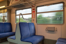Interior View Of A Corridor Inside Passenger Trains With Blue Fabric Seats Of German Railway Train System. Empty Vacant Passenger Car Inside The Tram.