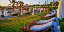 Cyprus,Paphos, Luxury Resort, Empty Sun Beds Umbrellas On The Green Hotel Grass