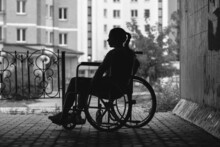 The Girl Is Sitting In A Wheelchair On A Gray Background. The Concept Of Bias Towards Disabled People, Depression, Disability.