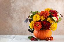 Bouquet Of Fresh Flowers In Pumpkin On Table Near Beige Wall