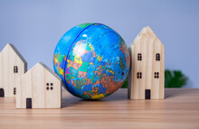 A Wooden Model House Is Placed Beside A Replica Globe. Placed On A Wooden Table With A Light Gray Background. Save World Concept