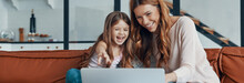 Young Beautiful Mother And Her Little Daughter Bonding Together And Smiling While Using Laptop At Home