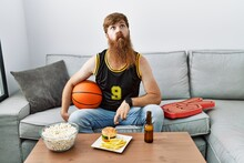 Caucasian Man With Long Beard Holding Basketball Ball Cheering Tv Game Making Fish Face With Lips, Crazy And Comical Gesture. Funny Expression.