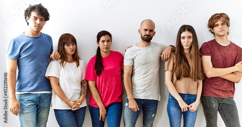 Carta da parati Group of young friends standing together over isolated background skeptic and nervous, frowning upset because of problem