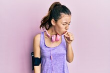 Young Brunette Woman Wearing Sportswear And Headphones Feeling Unwell And Coughing As Symptom For Cold Or Bronchitis. Health Care Concept.