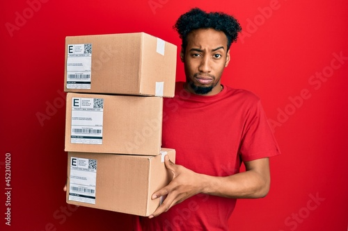 Carta da parati Young african american man with beard holding delivery packages skeptic and nervous, frowning upset because of problem